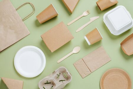Lay flat view set of eco-friendly disposable utensils and packaging made of bamboo wood and paper on a green background. Archivio Fotografico