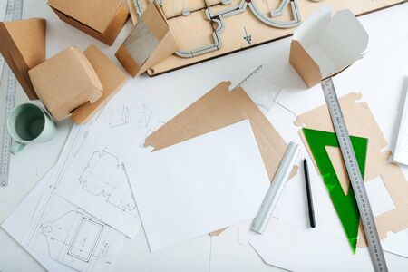 Top view of workplace packaging designer. Table with drawings, rulers and pencils, ready-made boxes and punching platen