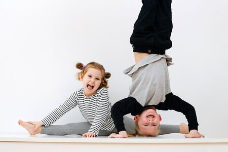 Portrait of children 5 and 7 years old, brother standing on his head and sister sitting on twine on a white background
