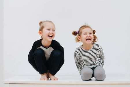 Playful brother and sister laugh sitting next to the white background of the house Foto de archivo