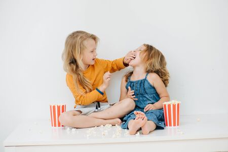 Sibling with blond hair in casual clothes have fun feeding each other popcorn