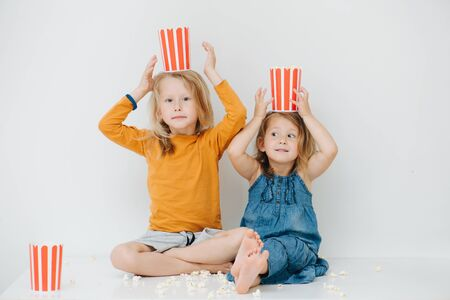 Sibling with blond hair in casual clothes are amused by making hats out of striped popcorn baskets