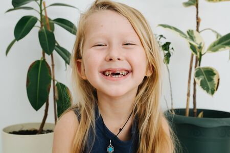 Natural change of teeth in a 7 year old boy with long blond hair shows his teeth Background of houseplants