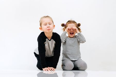 Sibling pretend, portray resentment and weeping through laughter on a white background 版權商用圖片