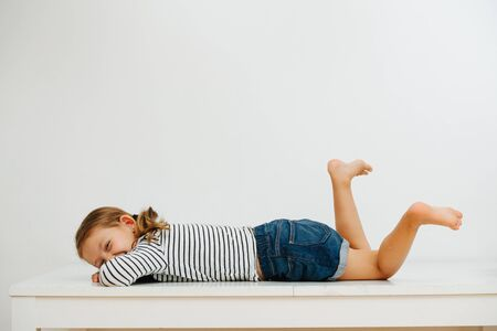 Girl in shorts and striped clothes lying on the table laughing and dangling legs 版權商用圖片