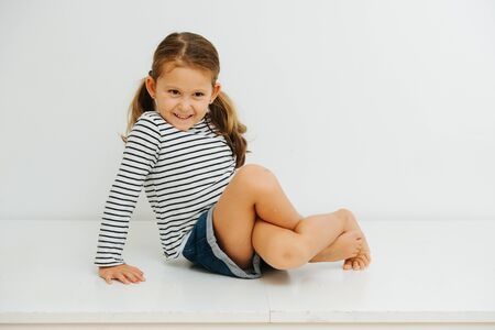 A 5-year-old girl with pigtails in casual clothes sits and twisting her legs 版權商用圖片