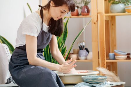 The concept of home hobbies. Woman in apron prepares to work behind a potter's wheel, sets a clay ball on it Stock Photo