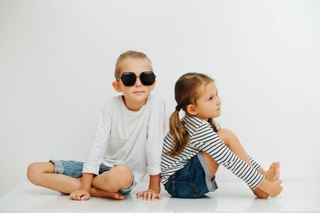 Thoughtful little barefoot siblings sitting on a table with their legs up. Both wearing jeans shorts and long-sleeves. Boy is wearing big funny sunglasses, girl holding her feet, immersed in a thought Stockfoto - 143661280