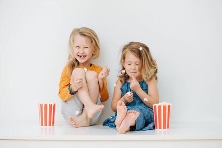 Misbehaving little barefoot siblings sitting on a table with their legs up. Over white wall. They are eating pop-corn and playing with it, throwing it in the air. Stockfoto - 143650377