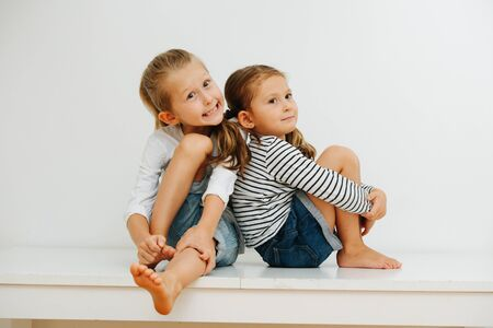 Funny little barefoot siblings sitting on a table with their legs up. Over white wall. Both wearing jeans shorts and long-sleeves. Stockfoto