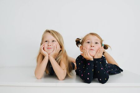 Adorable little barefoot siblings lying on a table with their feet up. Over white wall. Inflating their cheeks, leaning on hands, making cute faces for the camera. Both in nightware. Stockfoto
