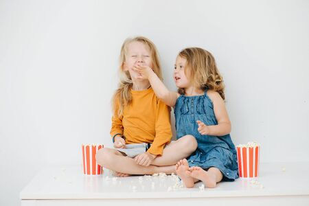 Misbehaving little barefoot siblings sitting on a table with their legs up. Over white wall. They are eating pop-corn, playing with it, girl tries to feed boy, he refuses to open his mouth and laughs. Stockfoto