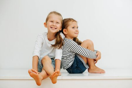 Funny little barefoot siblings sitting on a table with their legs up. Over white wall. Both wearing jeans shorts and long-sleeves. Boy is cheerful and girl is giving a perky look for camera.