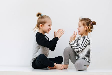 Immersed involved little barefoot siblings lying on a table with their feet up. Over white wall. Playing clap game. Both in nightware.