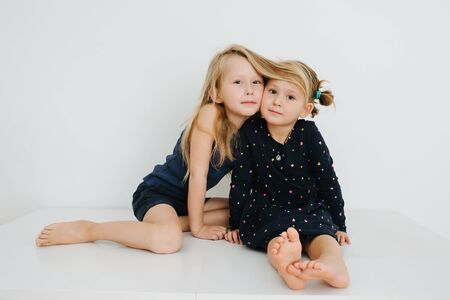 Lovely little barefoot siblings lying on a table with their feet up. Over white wall. Touching cheeks. Both in nightware.