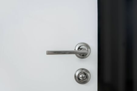 Metal handle with a lock on a white door. One of things you need to keep clean during covid-19 pandemic.