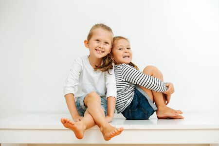 Happy little barefoot siblings sitting on a table with their legs up. Over white wall. Both wearing jeans shorts and long-sleeves. Boy sitting cross-legged and girl holding her legs. Stockfoto