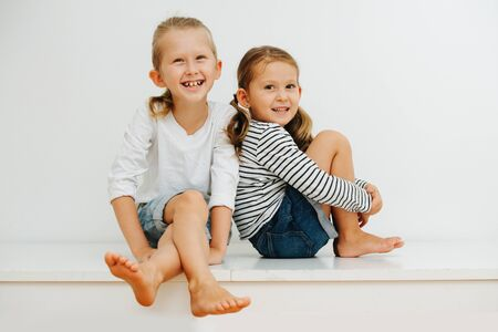 Happy little barefoot siblings sitting on a table with their legs up. Over white wall. Both wearing jeans shorts and long-sleeves. Boy sitting cross-legged and girl holding her legs.