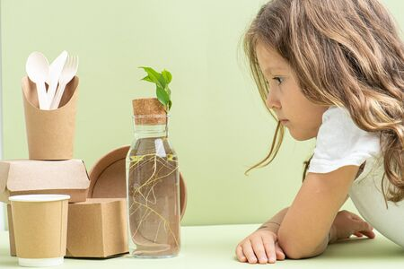 Little girl with long hair looking at composition of rooted branch in a glass bottle along with eco-frendly containers and cutlery over green background.
