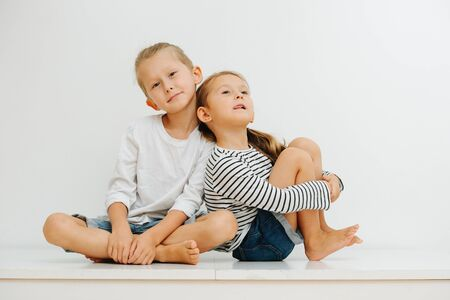 Funny little barefoot siblings sitting on a table with their legs up. Both wearing jeans shorts and long-sleeves. Boy sitting in easy pose and girl leaning on him, her tongue sticking out.