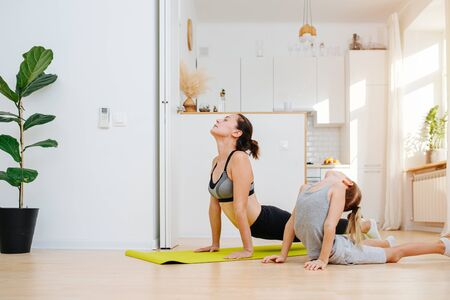 Family yoga class - a young mother and son of a schoolboy in a cobra pose on the floor against the background of white kitchen