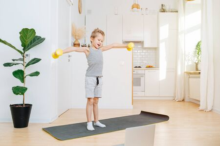 Morning online workout in the kitchen, the boy picks up dumbbells and smiles