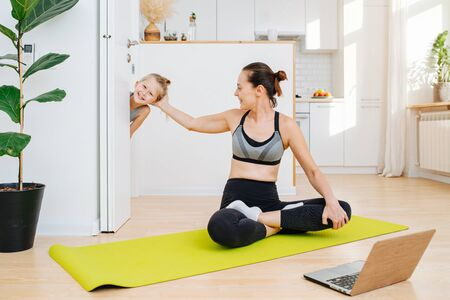 A young mother sits in a lotus pose on the floor and does an online yoga practise, while her son peeks into the room and distracts her mother. Banco de Imagens