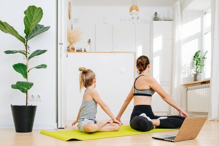 A young mother and schoolboy son do yoga over the background of white cuisine. They make a twisting pose in front of a laptop