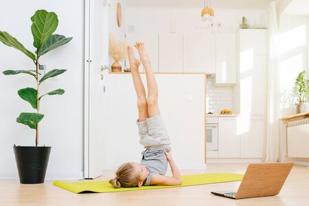 A schoolboy is doing online yoga class at home over a white kitchen background. He stands in a shoulderstand pose and looks into the computer.