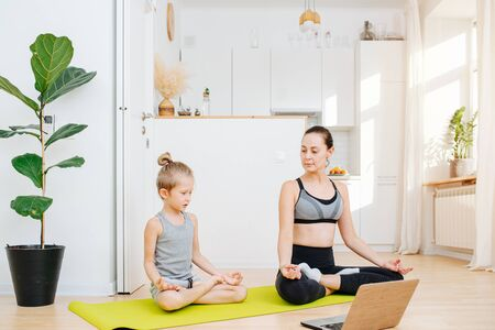 Home online yoga practice, mom and son sit in a lotus pose on the floor in front of the computer. In the background, a scandinavian-style light kitchen