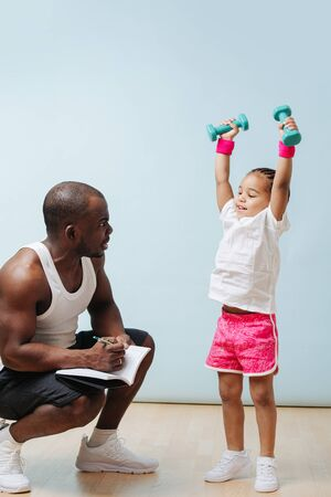Staying in the mood for physical activity during quarantine. Black father doing taking notes on his daughter lifting dumbbells. Stockfoto