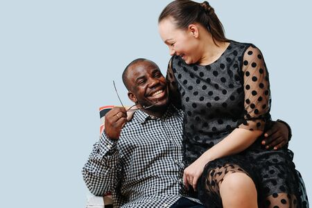 Happy mixed race mature couple spending time together during lockdown over blue background.