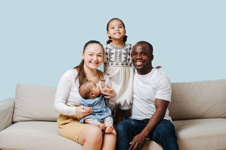 Cheerful mixed race family posing for a family photo in a studio. Black father, white moher and their two little daughters over blue background.