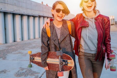 Two young happy smiling women with short hair in sunglasses are hugging and walking togeter, holding their skateboards. Sunset in a city. Gray floor and building.