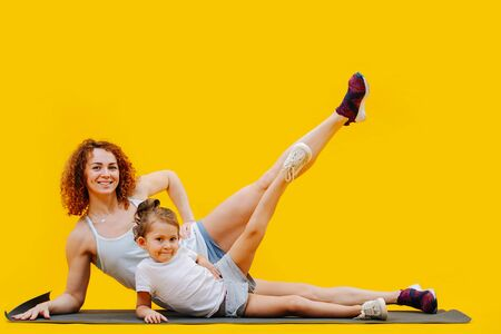 Mother and daughter doing side leg raises on a yoga mat, synchronous over yellow background