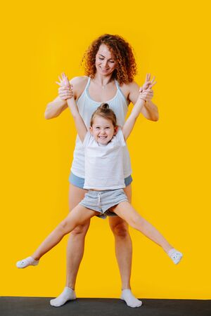 Mother and daughter gimnastic forms on a yoga mat over yellow background. Mom holding girl by her wrists in the air, while she extending her legs to sides.