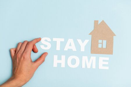 Hand placing cardboard letters with stay home message on a blue surface next to house shape