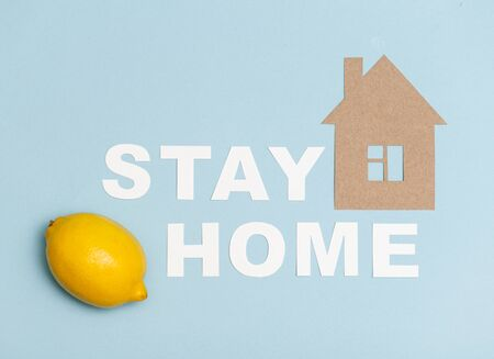 Cardboard stay home message laid on a blue surface along with house shape and one yellow loemon. Combat diseases with vitamin c.