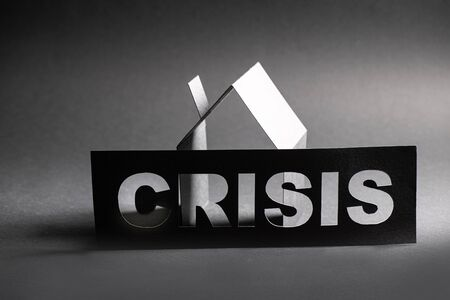 Crisis sign with cut out letters in front of cardboard house shape shades of gray background Banco de Imagens