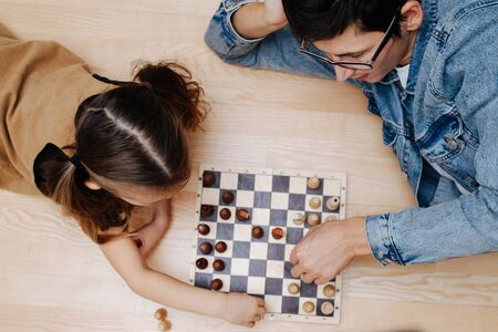 Happy father and his little daughter playing chess on a kitchen floor at home. Top view