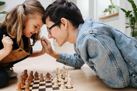 Happy father and his little daughter playing chess on a kitchen floor at home. Side view. Struggling over the board, pushing against each other's head and hands.