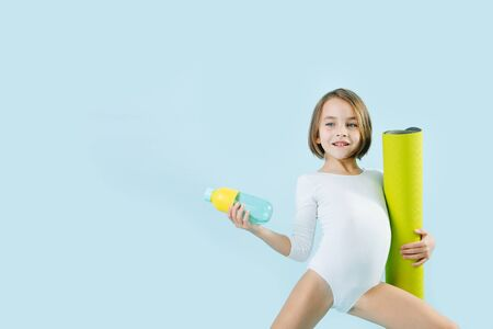 Little girl in a white leotard with rolled mat and water bottle over blue background. Standing in a gymnastic position.