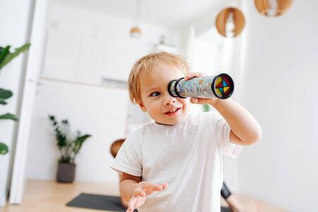 Fair little toddler boy looking into kaleidoscope. Blurred. Focus on a boy. At home Foto de archivo