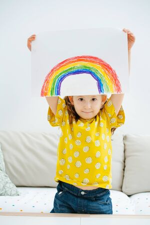 Little girl showing overhead a rainbow she just painted. She's sitting on a sofa in the living room.