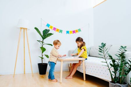 Little children drawing on a coffee table in a living room. Stay home flag garland hanging on the wall. Lonshot Banque d'images