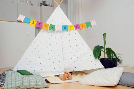Funny cute little kid's feet sticking out from under a hut, made with sticks and bedsheets. Stay at home flag garland hanging across the room overhead.
