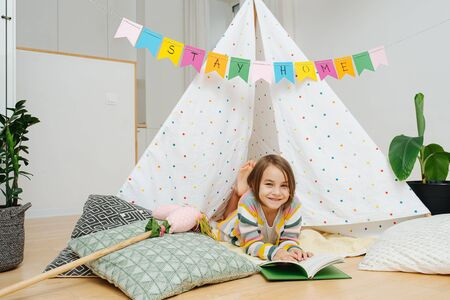 Immersed little girl lying on a blanket, reading book in front of a hut, made with sticks and bedsheets. Stay at home flag garland hanging across from wall to wall overhead.