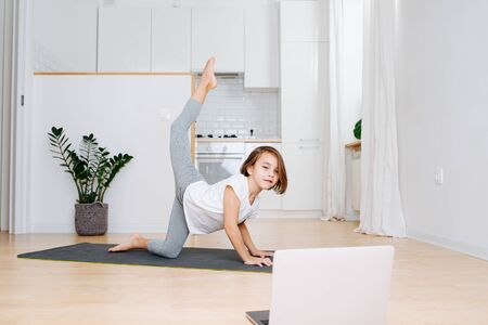 Little school age girl doing gymnastics on a yoga mat at home in isolation. Looking to laptop for instruction. Standing on three limbs, raising leg behind her back. Фото со стока