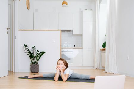 Little school age girl doing gymnastics on a yoga mat at home in isolation. Looking to laptop for instruction. She's sitting in splits, leaning chin on her hands. Фото со стока
