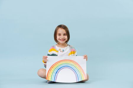 Cheerful little girl showing a rainbow she just painted. Sitting on the floor. Over blue background.